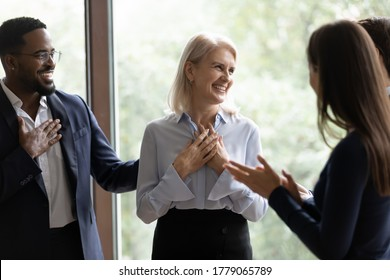 60s businesswoman staff member get praises congrats cheers compliments from multi ethnic colleagues. Promotion career advance, life events birthday celebration, warm relation, kindness from teammates