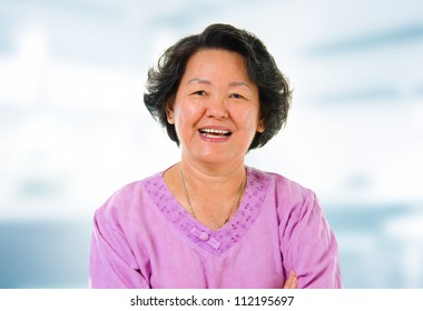 60s cheerful Asian senior woman smiling in home