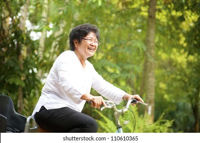 60s senior Asian woman riding on bicycle outdoor with great fun