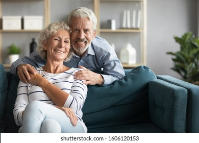 60s spouses photo shooting indoors, husband standing behind of wife embraces her, married couple smiling look at camera enjoy life feels happy looking healthy. Capture moment for family album concept
