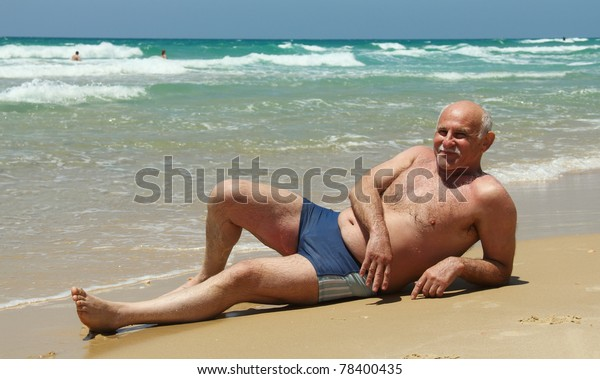 60-year-old man lying on the sand at the beach