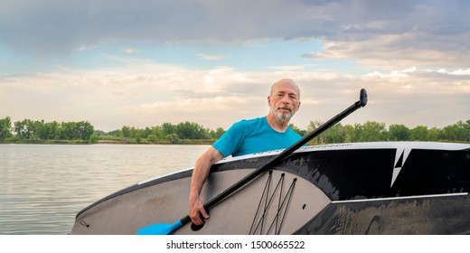 64 years old man with a stand up paddleboard after paddling workout on a lake in Colorado, active senior concept