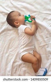 6-8-month-old baby boy lying playfully in bed. Charming 6-7 month little baby in white bodysuit. Baby boy in white bedding. Free space