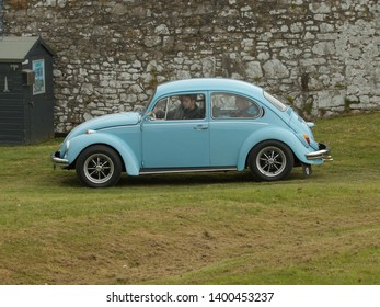 6th May2019- A classic Volkswagen Beetle saloon car being driven at a vintage vehicle show at Carew Castle near Tenby, Pembrokeshire, Wales, UK.