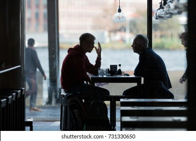6th October 2017; Amsterdam, The Netherlands; Two Men in Silhouette in Conversation Whilst Seated in a Cafe inside the Centraal Station.
