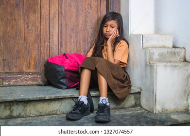 7 or 8 years child in school uniform sitting outdoors sad and depressed with her backpack on the stairs suffering bullying and abuse problem feeling alone and helpless in scared schoolgirl concept