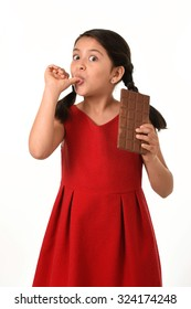 7 or 8 years old Hispanic girl wearing red dress holding big chocolate bar eating in happy and excited face expression licking her fingers in sugary nutrition and kids loving sweet concept