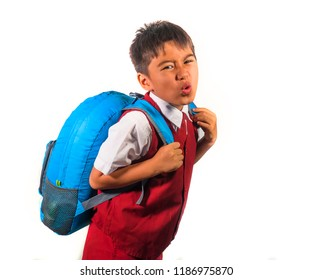 7 or 8 years old sweet kid in uniform carrying bag full of books feeling upset and complaining about the weight of the backpack in lazy schoolboy unhappy about going back to school