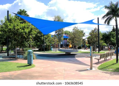 7 April 2018 Children park in Coffs Harbour, New South Wales, Australia. Sunny day time outdoors image of kids' park. In view are play area, bench, garbage bin, sail shade, trees, concrete surface