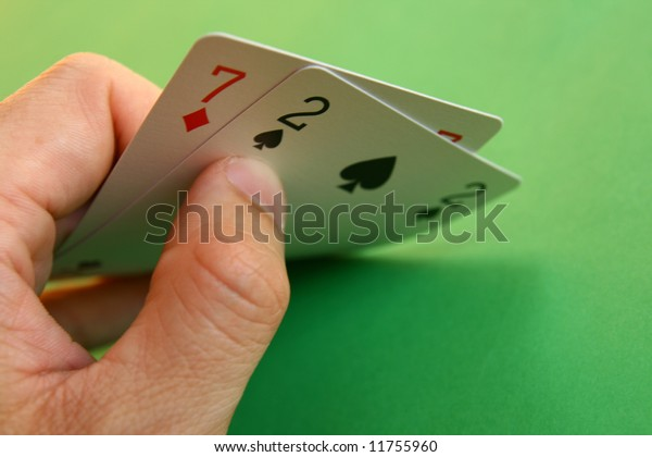7 diamond and 2 spade (bad cards) in the hand on green background...