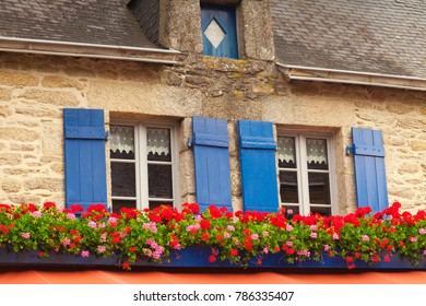 7 July 2011: Concarneau, Brittany, France - Two windows with lace curtains, blue shuitters and geraniums in window boxes in Concarneau, Brittany, France.