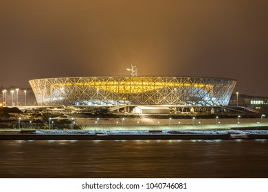 "7 March, 2018 Volgograd, Russia. New football stadium Volgograd Arena illuminated in the night, view from the other side of the Volga river. The monument ""The Motherland calls"" is standing on the back"