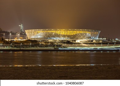 "7 March, 2018 Volgograd, Russia. New football stadium Volgograd Arena illuminated in the night, view from the other side of the Volga river. The monument ""The Motherland calls"" is standing on the left"