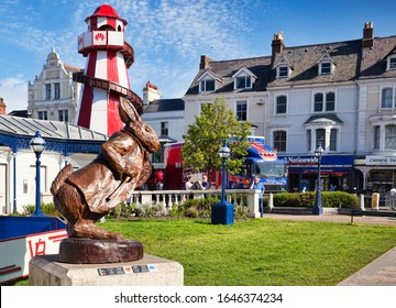 7 May 2018: Llandudno, Conwy, North Wales - White Rabbit oak sculpture, by Simon Hedger, part of the Alice in Wonderland Trail, with some of the attractions of Llandudno Victorian Extravaganza behind.