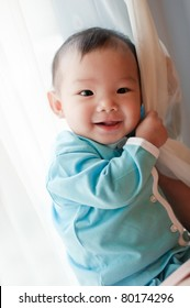 7 month old Asian baby girl smiling and holding on to a curtain