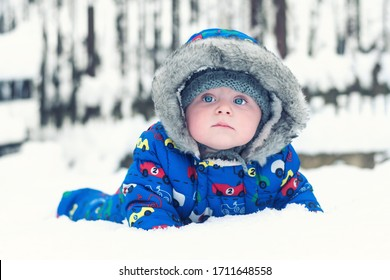A 7 month old Caucasian infant is lying in a blue hooded overall in his first snow in life.