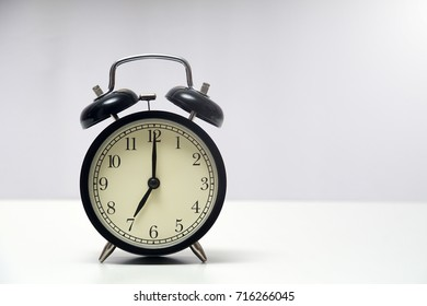 7 o'clock and 0 minutes over white background