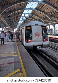 7 Oct 2017. Delhi Metro train arriving at Metro station in Delhi, India. Railway platform, train commuters, people walking on platform can be seen.