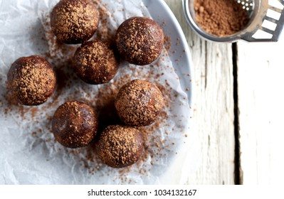 7 raw superfoods cacao protein balls dusted with cacao powder with a vintage tea strainer
