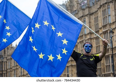 7 September 2017. Westminster London. The EU flag is held in the breeze by a masked protester in front of Westminster as part of an anti-Brexit protest at parliament