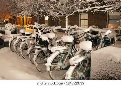 7 snow-covered bicycles are parked in the courtyard in The Netherlands
