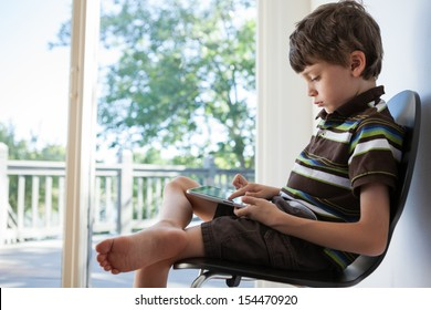 7 year old boy playing on a tablet pc in a sunroom