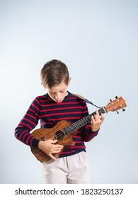 7 year old boy playing the ukelele, isolated on gray background