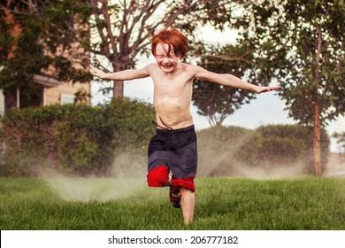 7 year old boy playing in the sprinkler on a hot day -- image taken outdoors in Reno, Nevada, USA