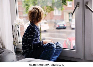 7 year old boy sitting near the window and looking to the street