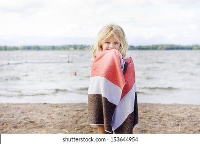 A 7 year old child wrapped up in a towel after a swim