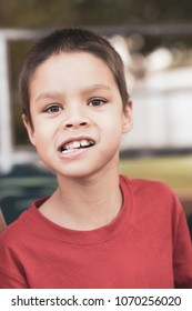 7 year old mixed race asian caucasian boy outdoors showing his crooked teeth. Red matte processing