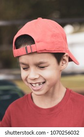 7 year old mixed race asian caucasian boy head and shoulders wearing backwards red baseball cap and red shirt at a school sporting event. Red matte processing