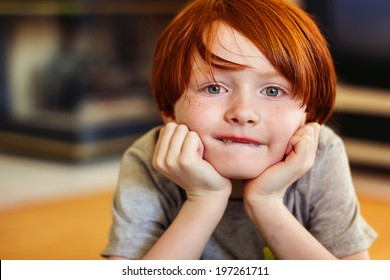 A 7 year old redheaded boy holding his head in his hands -- image taken indoors using natural light
