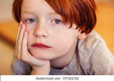 A 7 year old redheaded boy holding his head in his hands -- image taken indoors using natural light (Reno, Nevada, USA)
