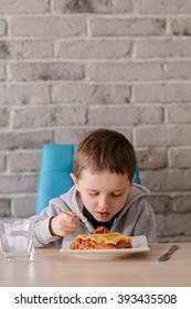 7 years old boy eating lasagne in dining room. Wears grey hoodie.
