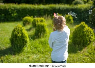 7 years old caucasian child boy blowing soap bubbles outdoor at sunset - happy carefree childhood.