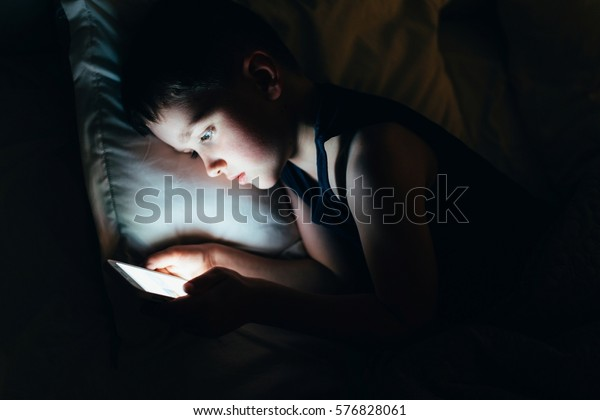 7 years old child boy using smartphone at night in bed