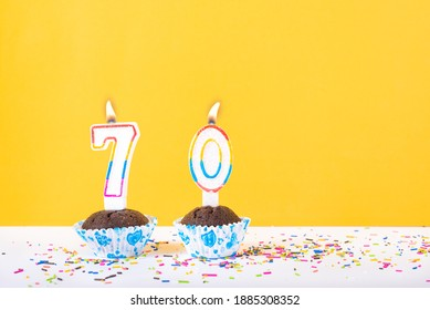 70 number candle on a cup cake with colorful sprinkles and yellow background seventieth birthday anniversary celebrations