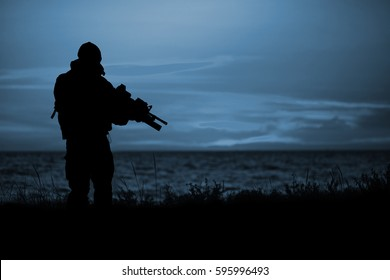 7/03 Silhouette of soldier with rifle on a sunset dark background. War, military and danger concept.