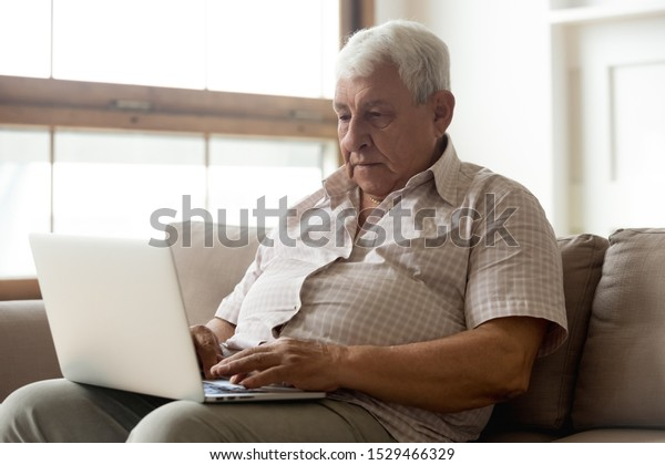 70s grey-haired man seated on couch using laptop, search clinic services medical insurance information, easy usage of medicine app for senior patient people, older generation and modern tech concept