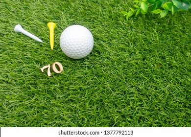 70th birthday with golf ball and tees are on green grass.