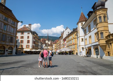 7/26/2019:  tourists and Ancient houses along Place des Halles. Camera facing Market Place des Halles in the city center of Neuchatel