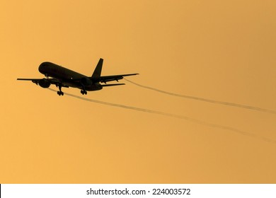 A 757 cleared for landing trailing vapor trails