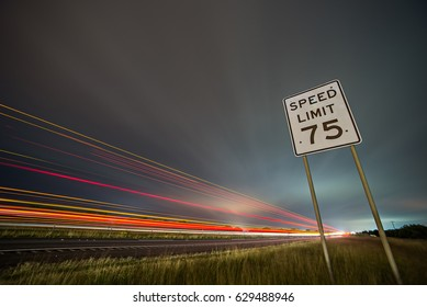 75np speed limit sign at night next to afreeway at night