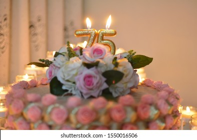 75th birthday cake with candles and roses