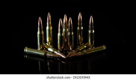 7.62mm ammunition cartridges standing and laid down on black background