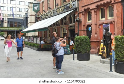 7th August 2018 Dublin. Tourism. Tourists strolling past popular heavy rock themed Bruxelles pub and a statue of Phil Lynott, deceased singer of Irish rock band Thin Lizzy, off Grafton Street.