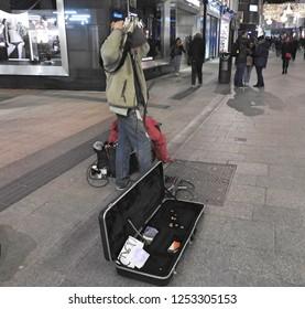 7th December 2018 Dublin. A busker playing a guitar behind his head on Grafton Street, Dublin at nighttime.