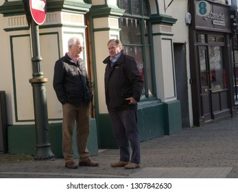 7th February 2019- Two men talking on a street corner in Lammas Street in the town center at Carmarthen, Carmarthenshire, Wales, UK.