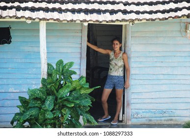 7th of November 2013 - Scene from Cuban farm with close up of a young woman standing in the doorway of a blue wooden house, Cienfuegos District, Cuba
